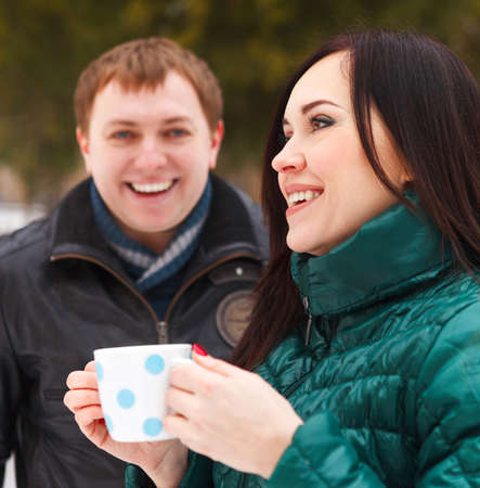 Happy young couple having fun in the winter park drinking hot tea photo