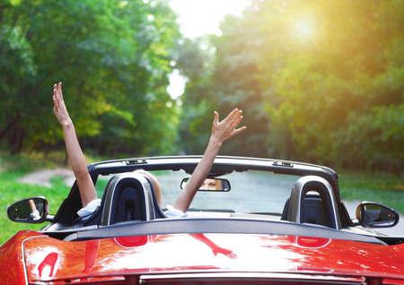 スポーツ車を運転して幸せな美しいブロンド若い女