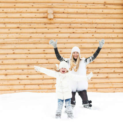 Happy mother with her daughter jumping outdoors in a winter day photo