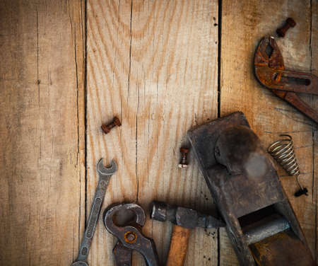 Dirty set of hand tools on a wooden background photo