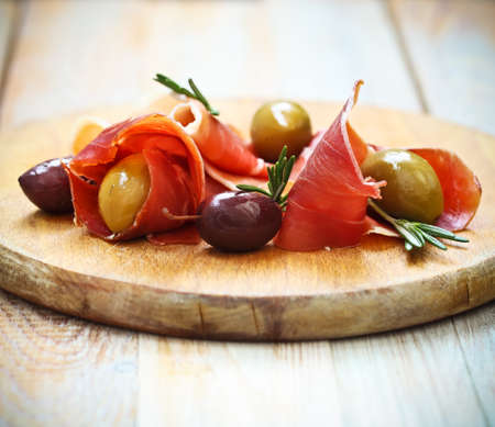 prosciutto: Prosciutto with olives and rosemary on the wooden background Stock Photo