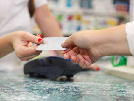 Close up of human hands holding credit card in drug store