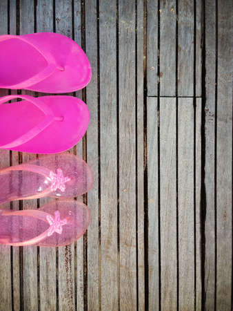 Brightly colored pink flip-flops of a mother and daughter on wood. Family vacation Stock Photo - 23780274