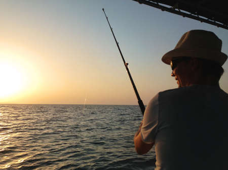 ocean fishing: Young man fishing on a ocean from the boat at sunset