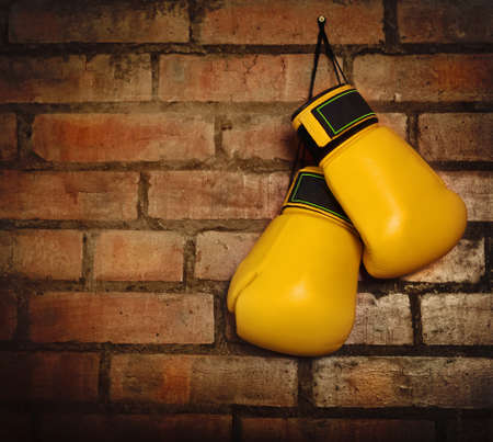 quiting: Pair of yellow boxing gloves hanging on a brick wall