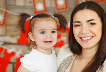 Happy smiling mother with daughter near the Christmas background Stock Photo - 24177659