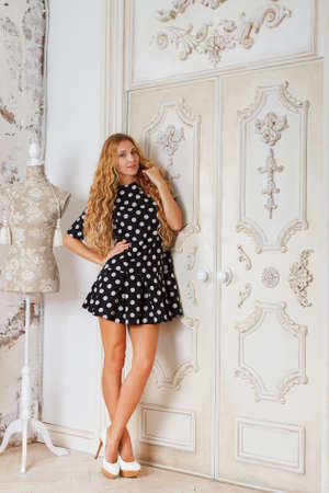Portrait of the beautiful blond girl in polka dots dress in living room photo