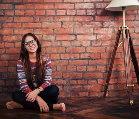 Close up portrait of a beautiful cute teen girl sitting on the floor photo