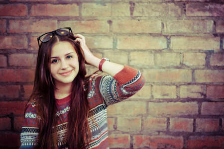 close portrait: Close up portrait of a beautiful cute teen girl smilling near the brick wall Stock Photo