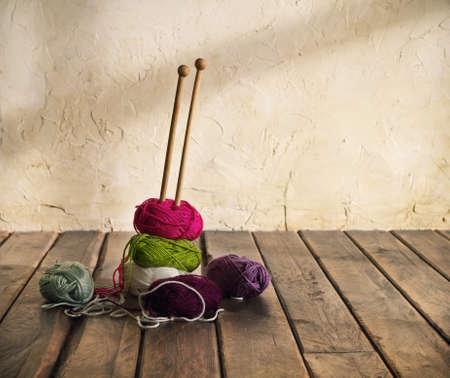 Colorful balls of yarn on a wooden table. Retro style photo