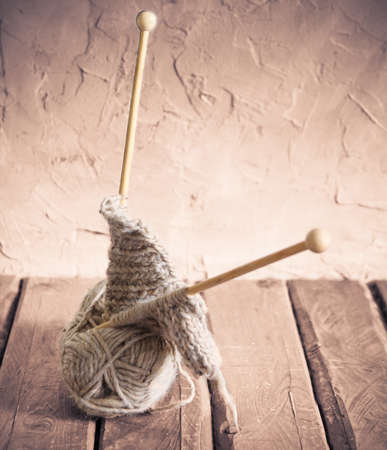 Balls of yarn and knitting on a wooden table. Retro style photo