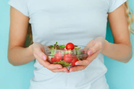 close up food: Woman diet concept portrait. Female model holding green salad Stock Photo