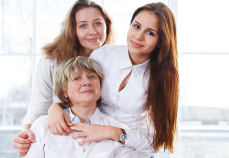 Close up portrait of a mature mother and adult daughter and teen granddaughter being close and hugging at home being happy and joyful  photo