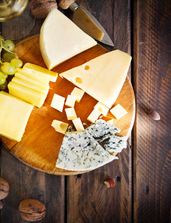 winy: Glass of white wine, cheese, nuts and grapes on the wooden background
