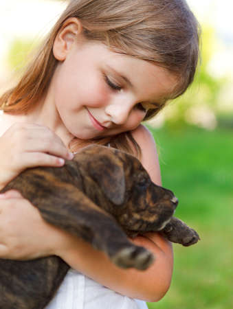 Cute little girl hugging her dog puppy. Sunny day. Friendship and care concept