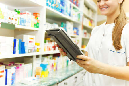 Pharmacist working with a tablet computer in the pharmacy holding it in her hand while reading information photo