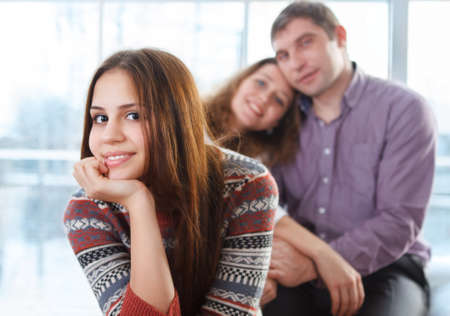 madre e hija adolescente: Sonriendo feliz adolescente sentado en frente de sus padres