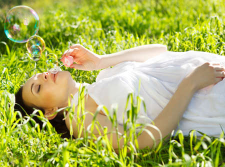 pregnant jeans: Beautiful pregnant woman relaxing on grass in the spring park Stock Photo