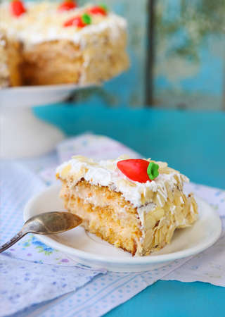 carrot cake: Piece of carrot cake with icing and little carrot on blue wooden table