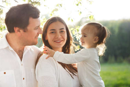 latin family: Happy young family with baby girl in the spring park