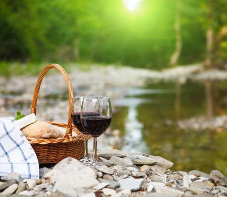Red wine, cheese and bread served at a picnic.