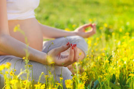 pregnancy exercise: Healthy pregnant woman doing yoga in nature outdoors. Close up Stock Photo