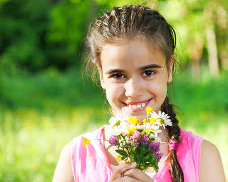Close up portrait of little smiling girl with spring flowers bouquet photo