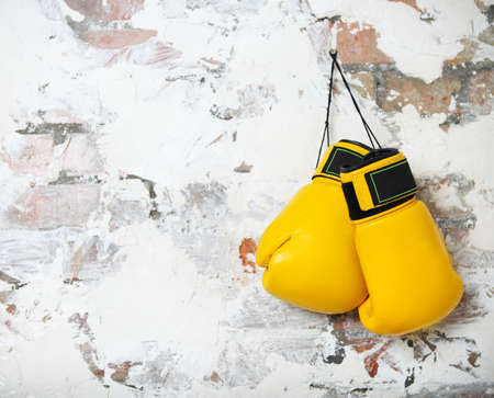 Pair of yellow boxing gloves hanging on a brick wall photo