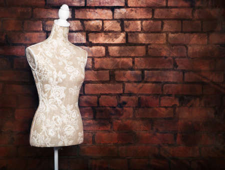 female form: Antique dress form with vintage look against brick