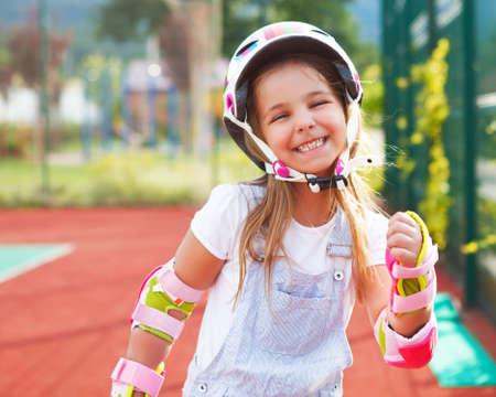 niño en patines: Niña en patines en el parque infantil