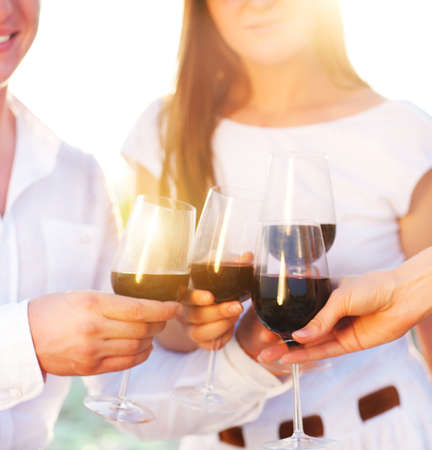 Celebration. People holding glasses of red wine making a toast Stockfoto