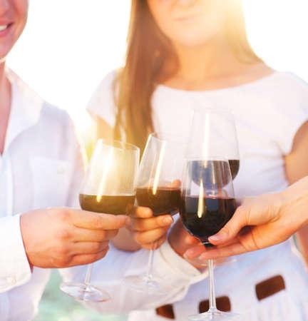 Celebración. Personas que tienen vasos de vino tinto hacer un brindis