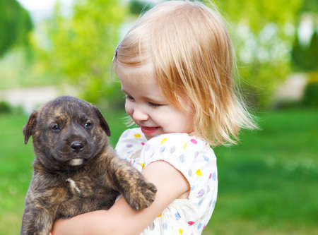 outside of the country: Cute little girl hugging dog puppy