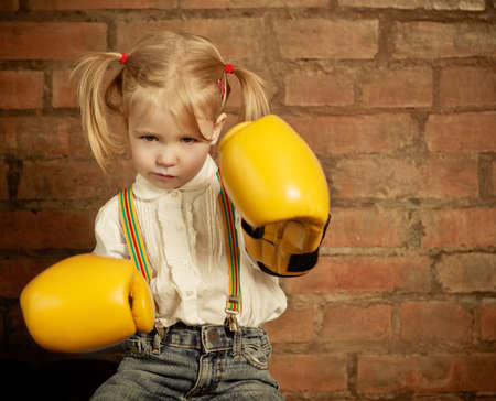 Little girl with yellow boxing gloves over brick wall background