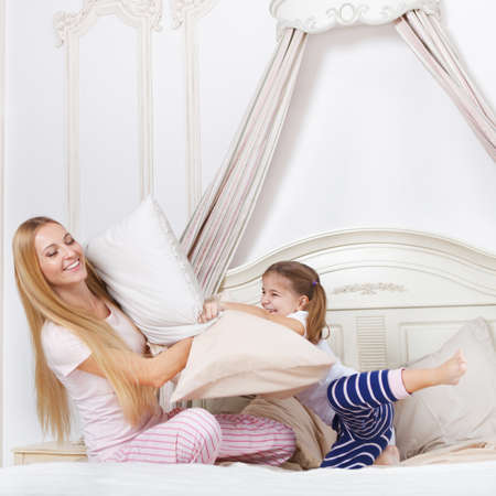 Cheerful family having pillow fight in a bedroom photo