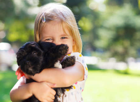 Cute little girl hugging dog puppy outdoors. Friendship and care concept photo