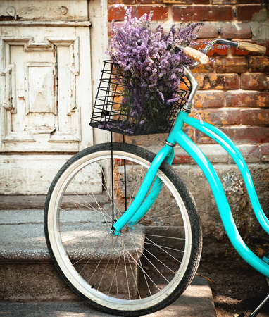 Vintage bycycle with basket with lavender flowers near the old wooden door