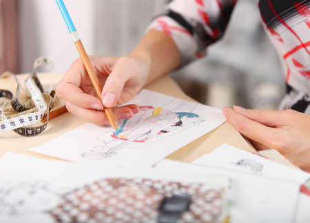 Dressmaker is drawing a fashion sketch. Close up of the hands