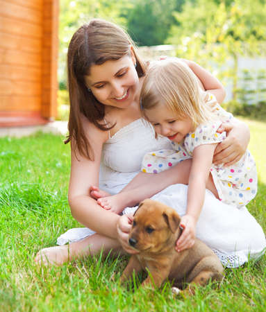 Cute little girl and her mother hugging dog puppies. Friendship and care concept photo