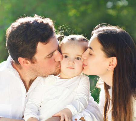 mums: Happy young family with baby girl outdoors Stock Photo