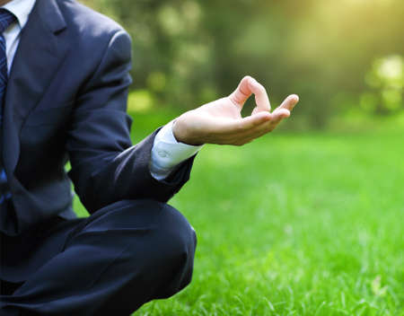 Business man relaxing in a park in the lotus position. Close up photo