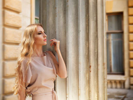Beautiful blond woman in beige long dress outdoors photo