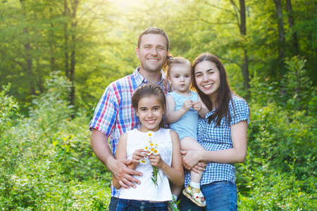 Happy young family with two children in the spring forest photo