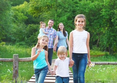 Happy young family with four children outdoors photo