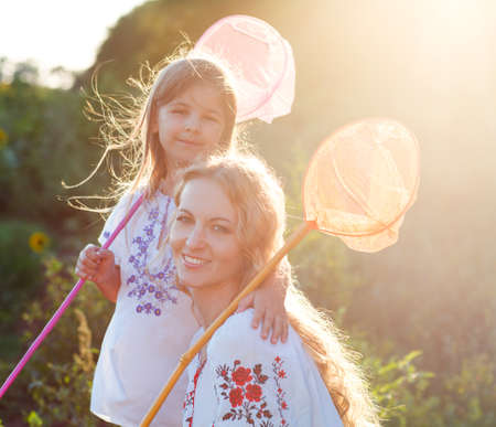 Cheerful mother and her daughter playing in a field with insect net in summer evening photo