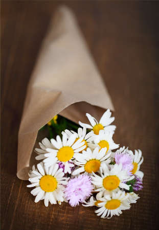 Small bouquet of wildflowers on a rustic table at country cottage photo