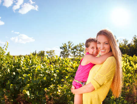 Happy mother and her little daughter in the harvest time in the vineyard Stock Photo