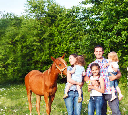 Happy young family with four children and baby horse in the spring forest photo