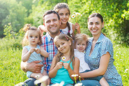 Happy young family with four children in the spring forest photo