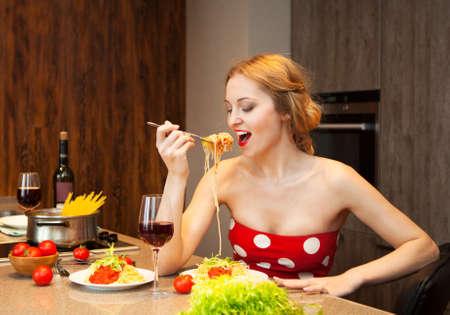 집에서 스파게티를 먹는 섹시한 젊은 금발의 여자 스톡 콘텐츠
